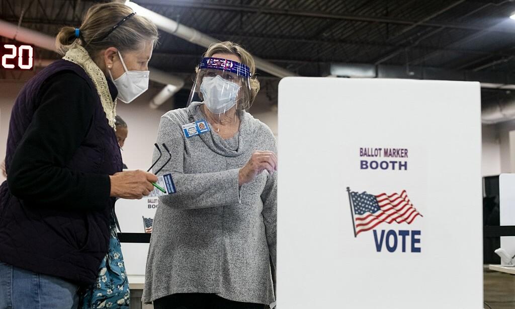 Tình nguyện viên hướng dẫn cử tri tại điểm bỏ phiếu sớm tại Ohio ngày 6/10. Ảnh: AFP.