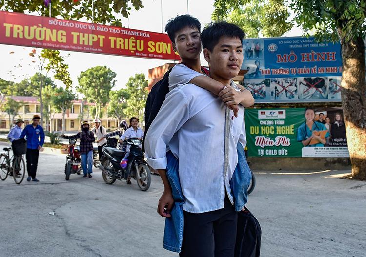 Hơn 10 năm qua, Ngô Văn Hiếu mỗi ngày đều cõng bạn đến trường. Ảnh: Lam Sơn.