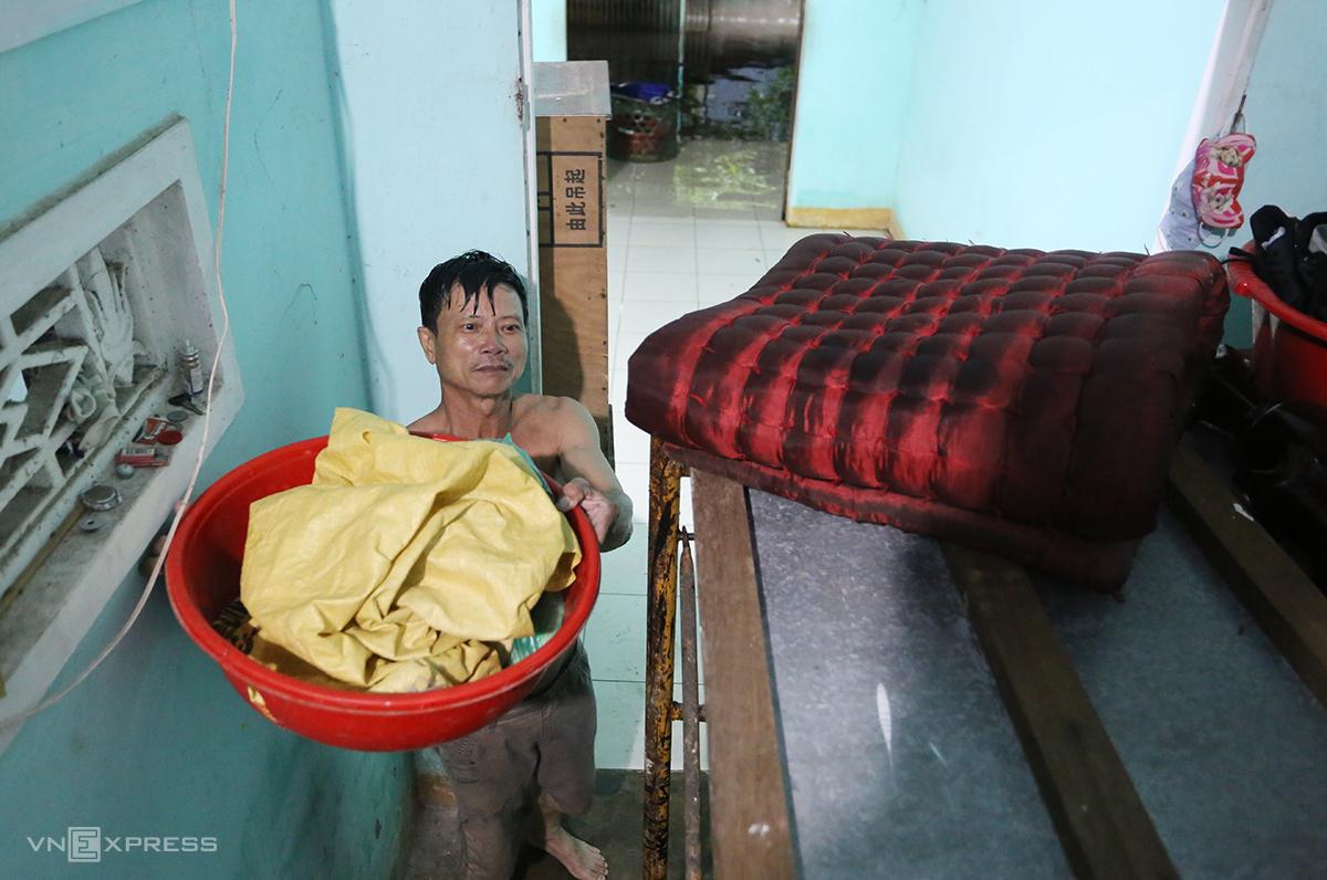 Anh Kim đưa đồ đạc lên cao tránh lũ lụt. Ảnh: Đắc Thành.