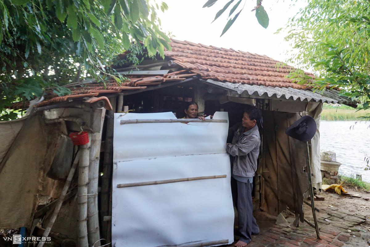 Vợ chồng ông Đa bà Thủy sửa lại cửa của ngôi nhà giữa sông trước mùa Đông. Ảnh: Phạm Linh.