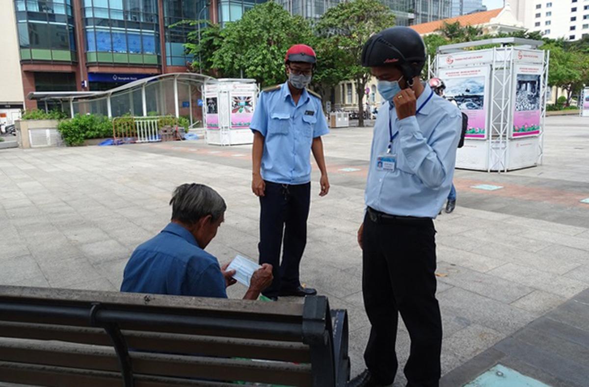 Đội trật tự đô thị phường Bến Nghé, quận 1 nhắc nhở một người dân không đeo khẩu trang ở phố đi bộ Nguyễn Huệ, ngày 5/8. Ảnh: Hà An.