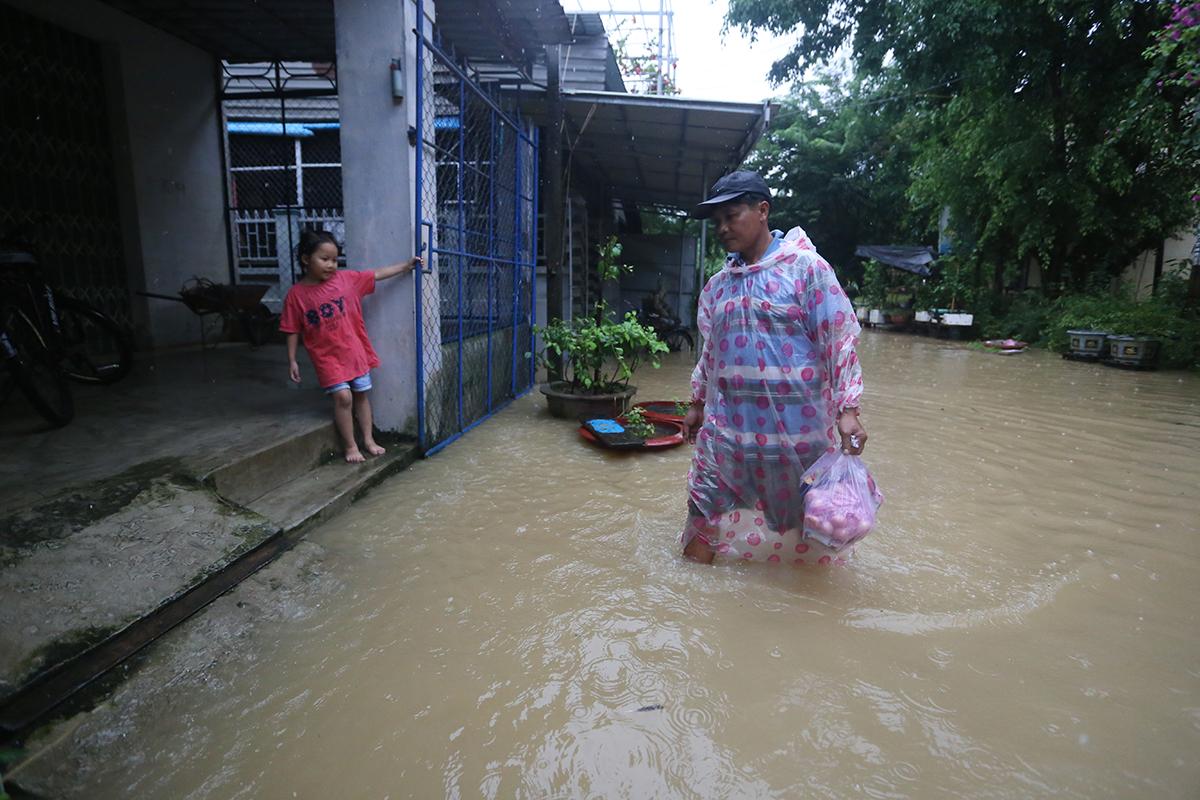 Anh Ba lội nước lũ ra chợ mua thực phẩm sử dụng trong những ngày mưa lũ kéo dài. Ảnh: Đắc Thành.