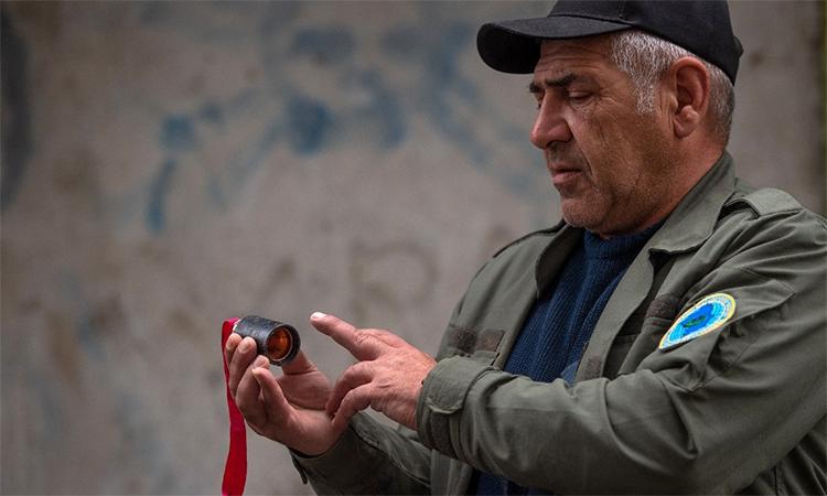 Một người đàn ông cầm vật nghi là do bom chùm rải xuống thành phố Stepanakert, vùng Nagorno-Karabakh, ngày 4/10. Ảnh: AFP.