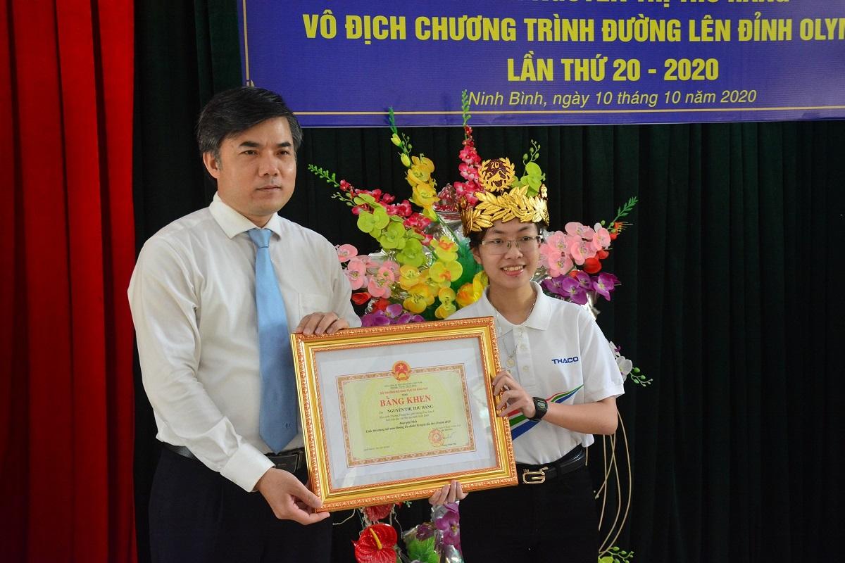 Ông Bùi Văn Linh trao bằng khen cho Thu Hằng tại trường THPT Kim Sơn A, sáng 10/10. Ảnh: MOET