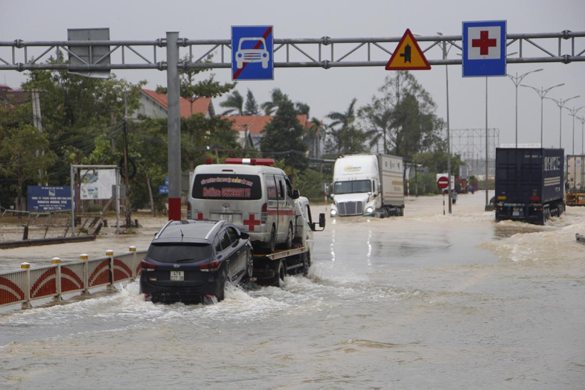 Nhiều xe ôtô con phải nhờ xe cứu hộ mới qua được đoạn đường ngập. Ảnh: Võ Thạnh