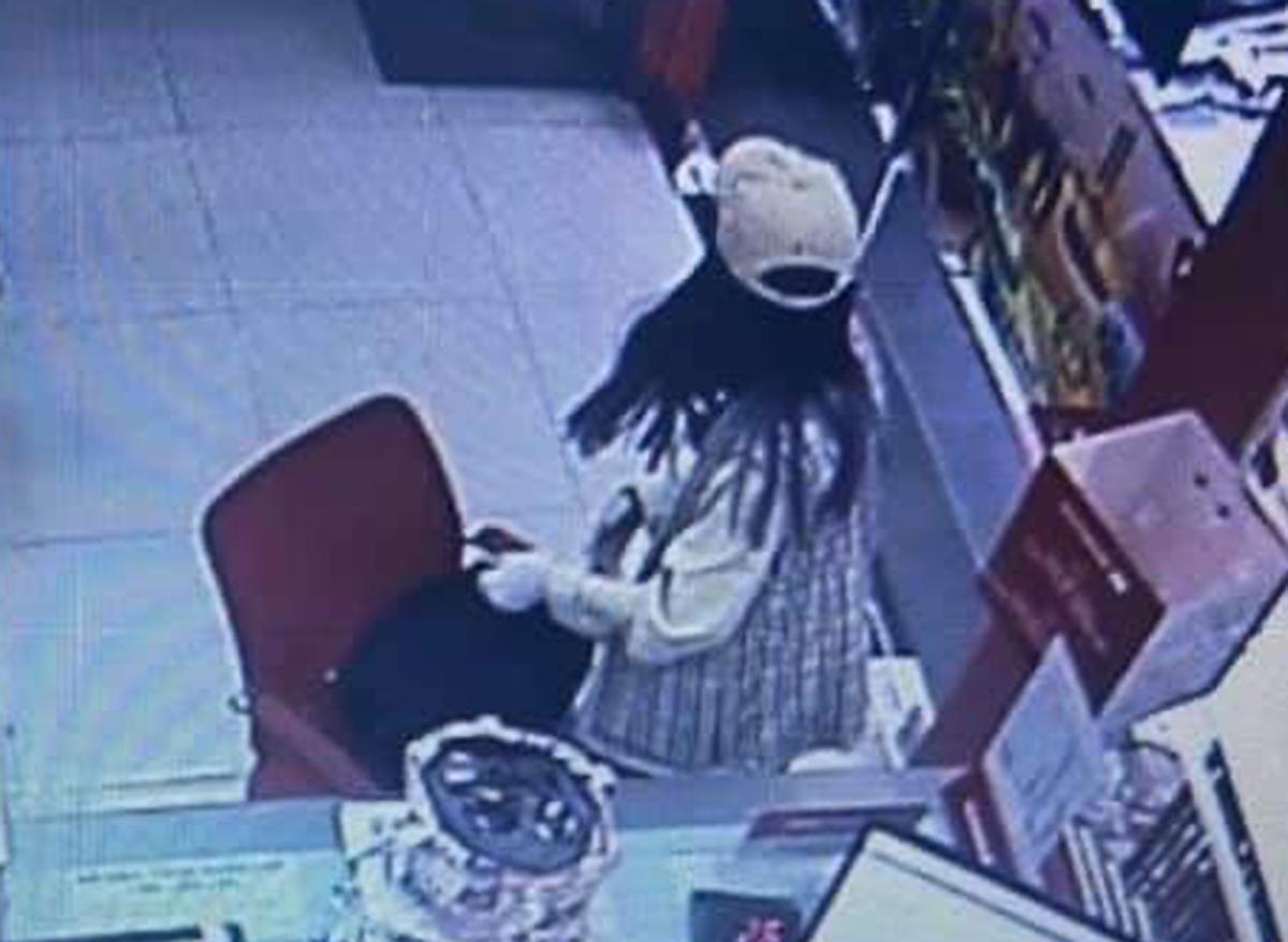 Người đàn bà gom tiền cướp được, chuẩn bị tẩu thoát. Ảnh cắt từ camera an ninh.