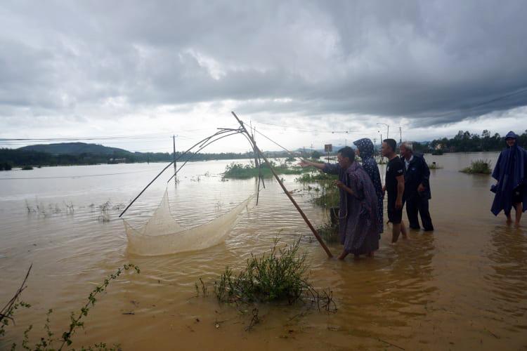 Con đường xã Bình Minh, huỵên Bình Sơn ngập nước, người dân mang lưới kéo cá, chiều 11/10. Ảnh: Phạm Linh.