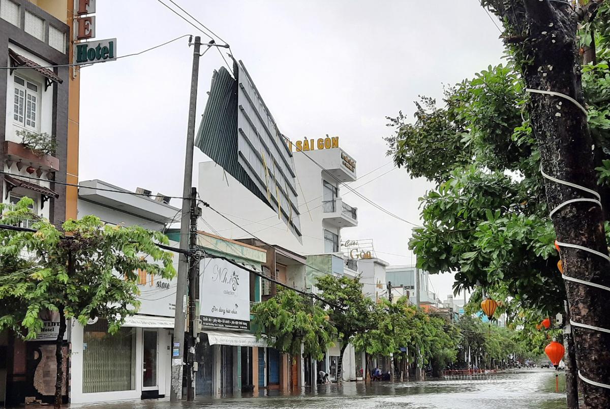 Một phần mái nhà bay lên đường dây điện trên đường Huỳnh Thúc Kháng, TP Tam Kỳ. Ảnh: Đắc Thành.