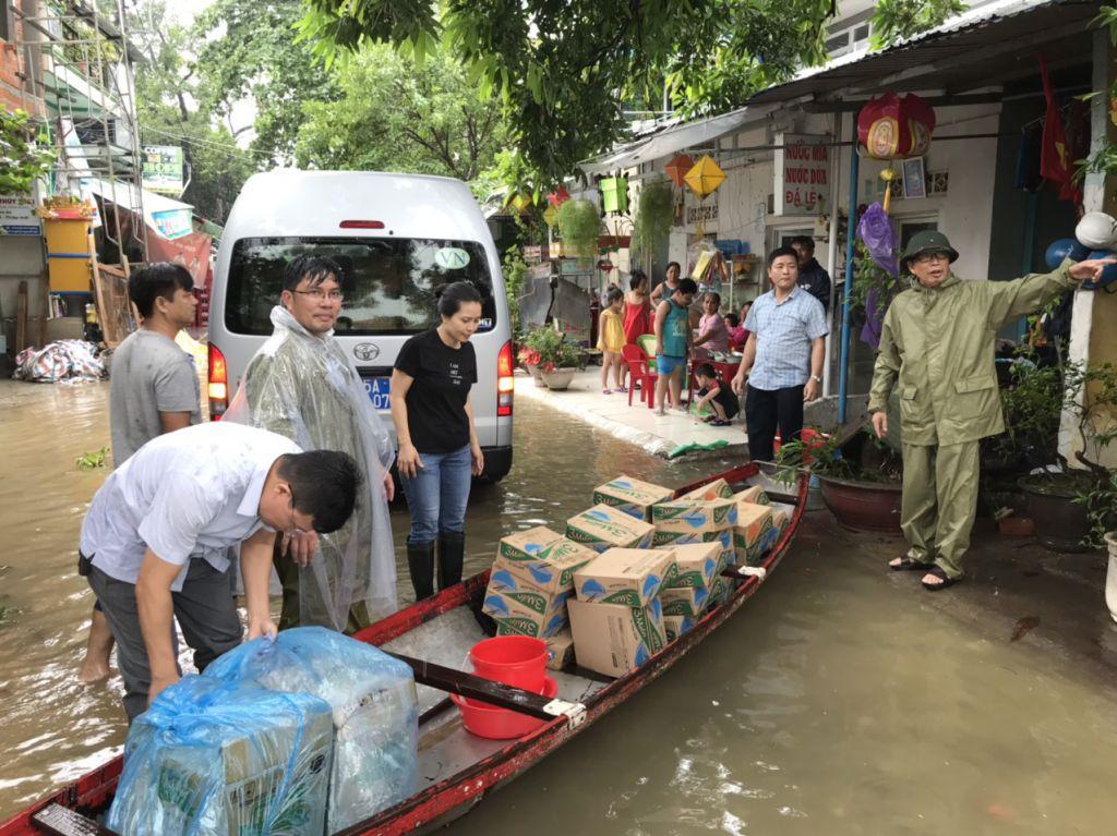 Giám đốc Đại học Huế (bên phải) cùng đại diện trường tiếp tế lương thực và nhu yếu phẩm cho sinh viên bị kẹt lại vì lũ. Ảnh: MOET