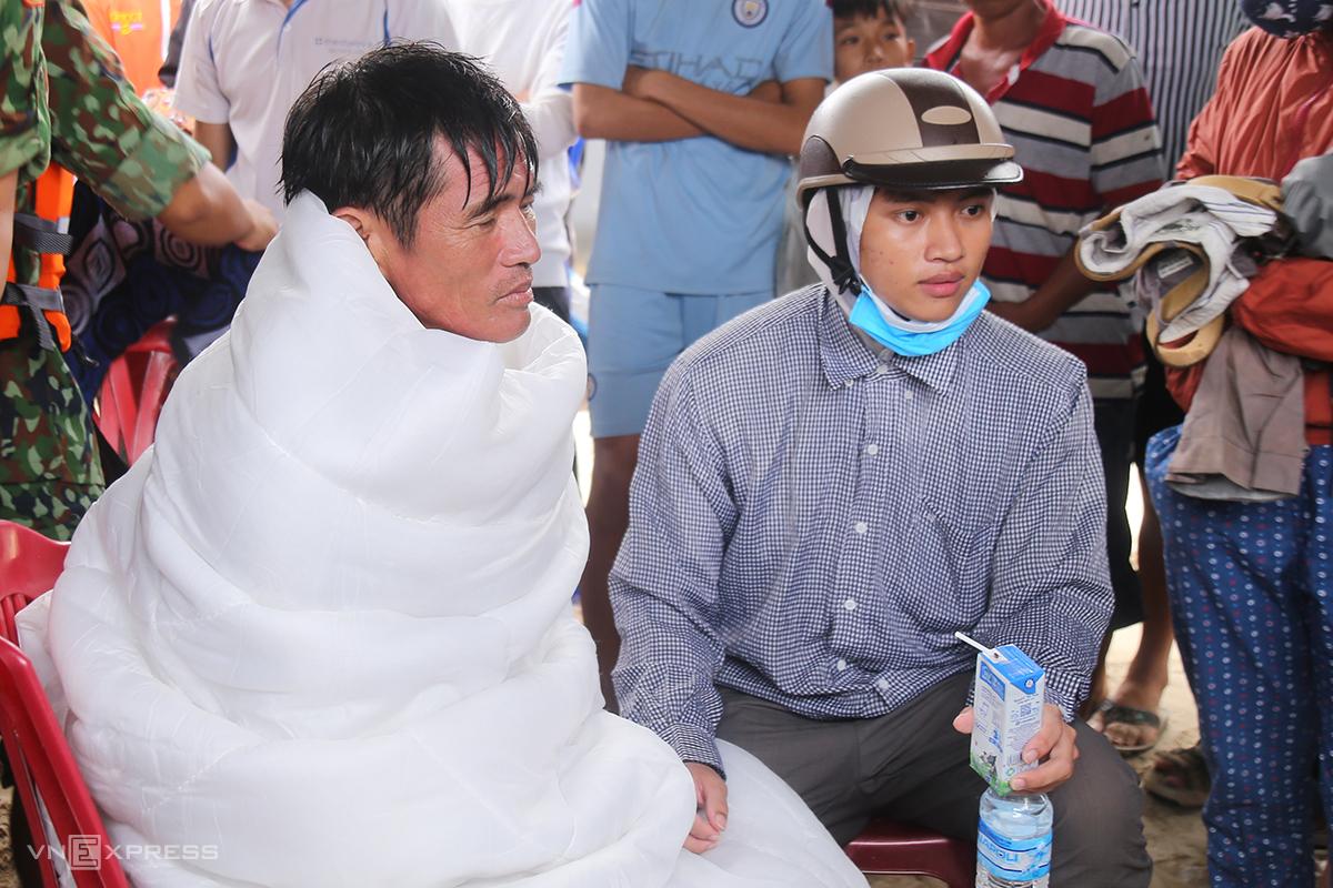 Ngư dân Nguyễn Hoài Xanh cung cấp thông tin về các thuyền viên, tình hình sóng gió với lực lượng cứu nạn, sau khi được đưa về bờ, lúc 16h04 ngày 10/10. Ảnh: Hoàng Táo