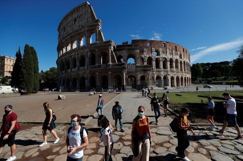 Người dân đi qua Đấu trường La Mã ở Rome, Italy ngày 8/10. Ảnh: Reuters.