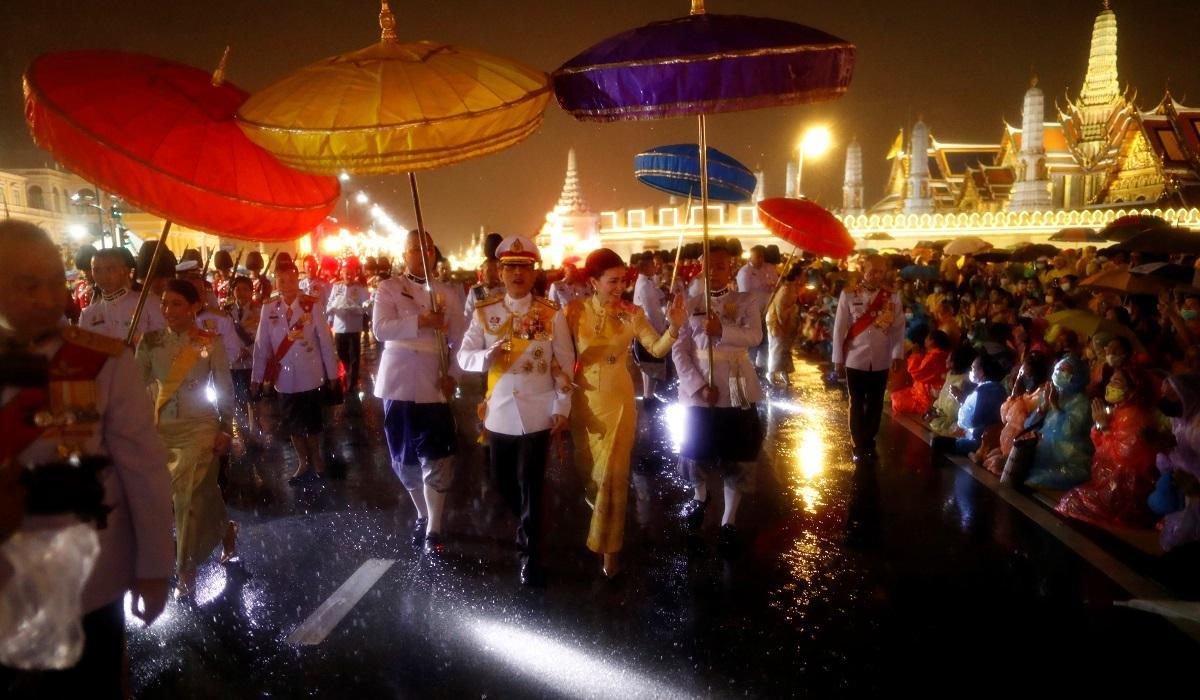 Nhà vua Maha Vajiralongkorn và Hoàng hậu Suthida chào người ủng hộ dưới mưa ở bên ngoài hoàng cung tối 13/10. Ảnh: Reuters.