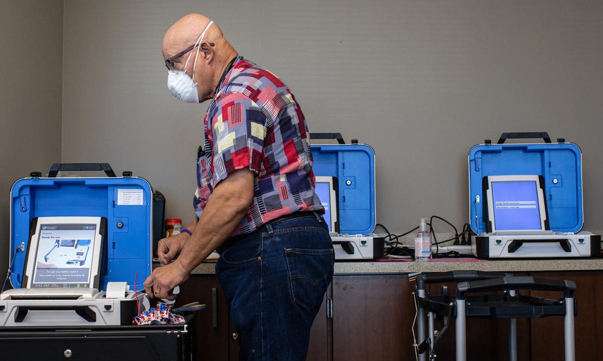 Nhân viên bầu cử kiểm tra hệ thống máy móc đăng ký  trước giờ bỏ phiếu ở San Marcos, bang Texas hôm 13/10. Ảnh: NYTimes.