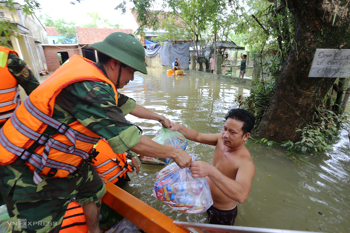Quân đội dùng canô vượt lũ phát lượng thực cho người dân xã Tam Đàn, huyện Phú Ninh sáng 12/10. Ảnh: Đắc Thành
