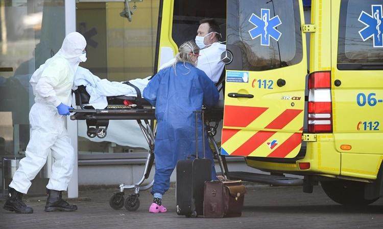 Nhân viên y tế di chuyển một bệnh nhân nghi nhiễm nCoV bên ngoài bệnh viện Bernhoven ở Uden, Hà Lan, hồi tháng ba. Ảnh: Reuters.
