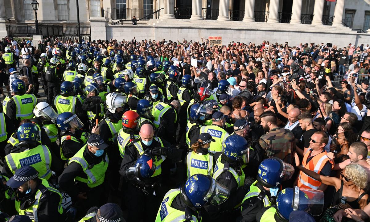 Cảnh sát Anh cố gắng ngăn người biểu tình phản đối vaccine và các biện pháp hạn chế phòng ngừa Covid-19 tại quảng trường Trafalgar ở London tháng trước. Ảnh: AFP.