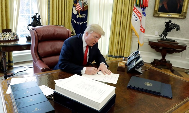 Tổng thống Trump ký đạo luật cắt giảm thuế doanh nghiệp và thuế thu nhập cá nhân ngày 22/12/2017. Ảnh: AP.