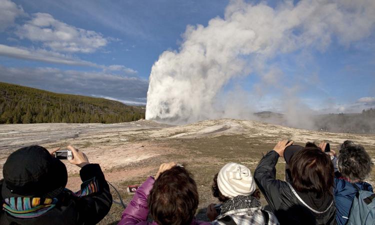 Khách tham quan chiêm ngưỡng mạch nước Old Faithful phun trào. Ảnh: AP Photo/Julie Jacobson.