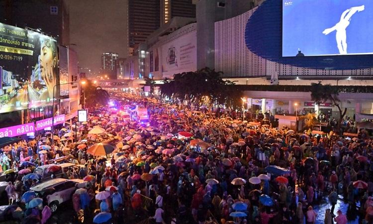 Người biểu tình ở Bangkok, Thái Lan dùng ô che chắn khi cảnh sát dùng vòi rồng giải tán đám đông tối 16/11. Ảnh: AFP.