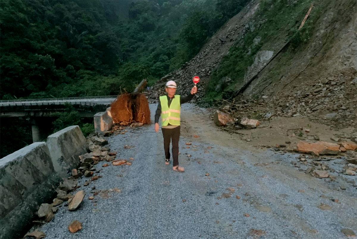 Nhà chức trách hướng dẫn các phương tiện đi qua khu vực sạt lở trên quốc lộ 8A ở xã Sơn Kim 1. Ảnh: Đức Hùng
