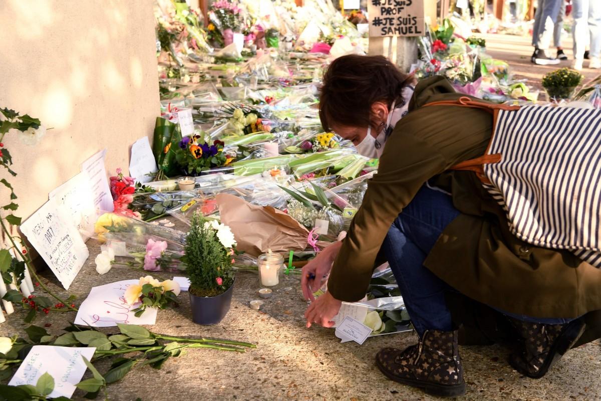 Một người phụ nữ đặt hoa tưởng niệm giáo viên Samuel Paty tại trường Conflans-Sainte-Honorine ngày 17/10. Ảnh: AFP.