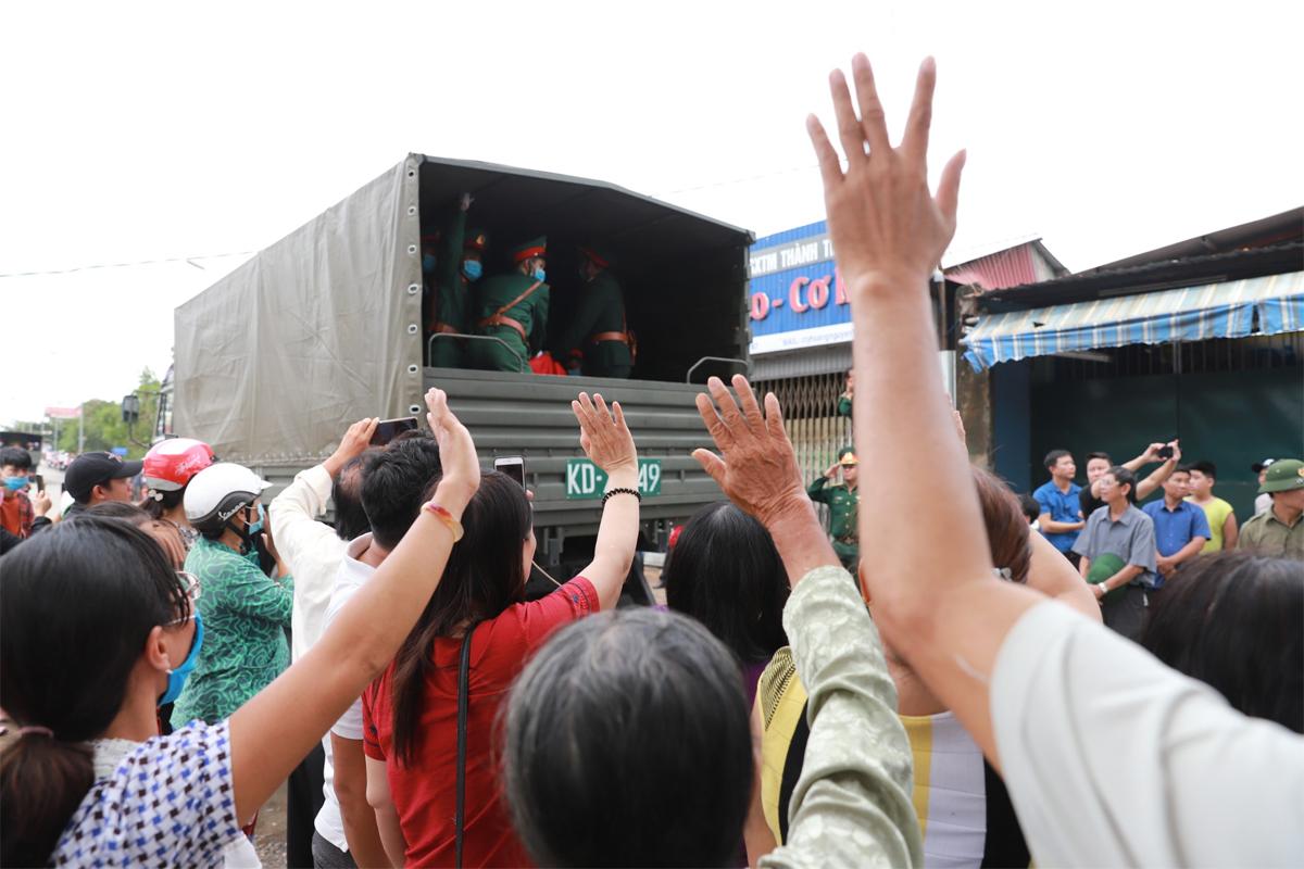 Người dân đứng hai bên đường chào tiễn biệt các liệt sĩ khi đoàn xe đi qua. Ảnh: Nguyễn Đông