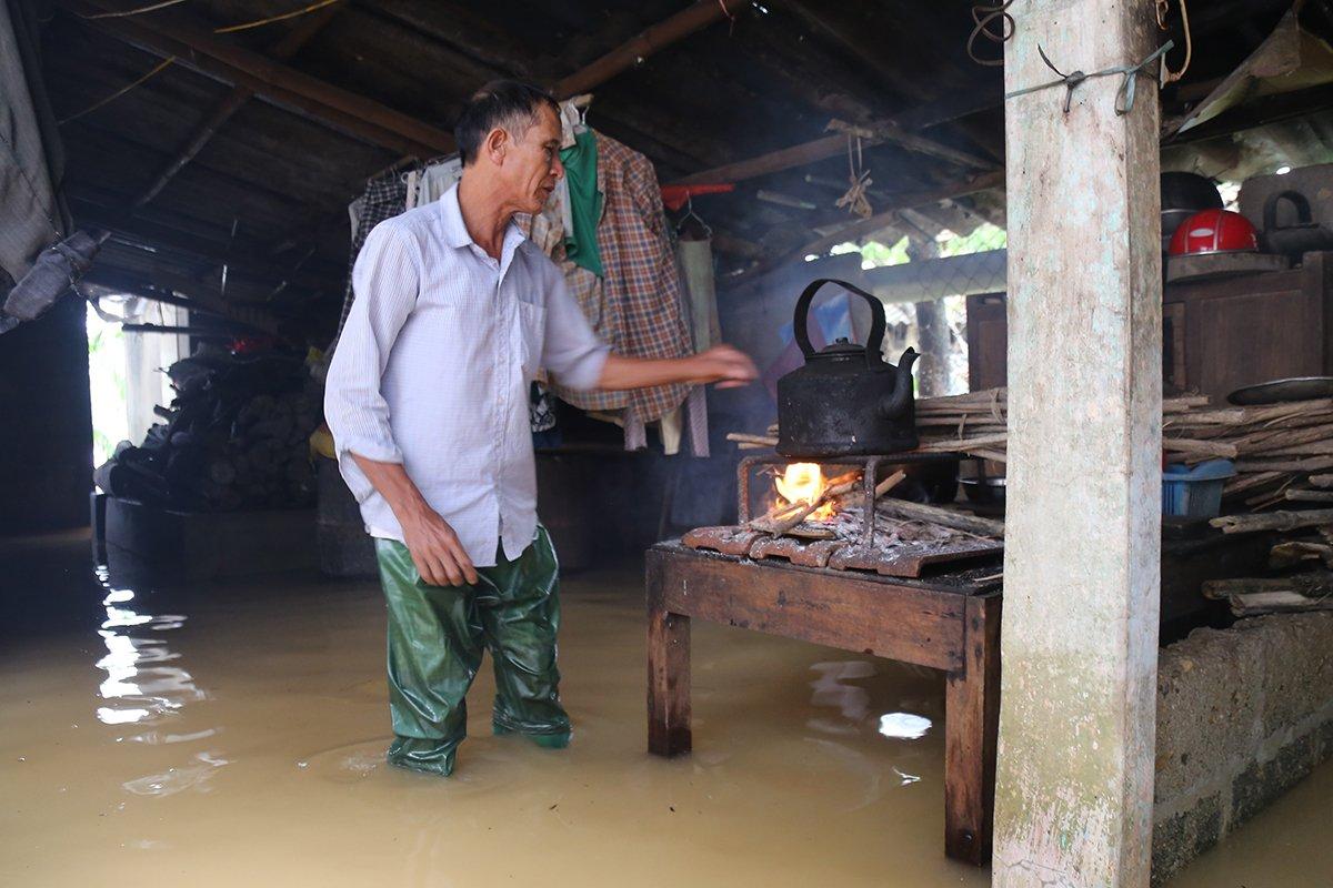 Ông Nguyễn Văn Liễu lội trong nước , thay vợ nấu ăn ngày lũ. Ảnh: Hoàng Táo