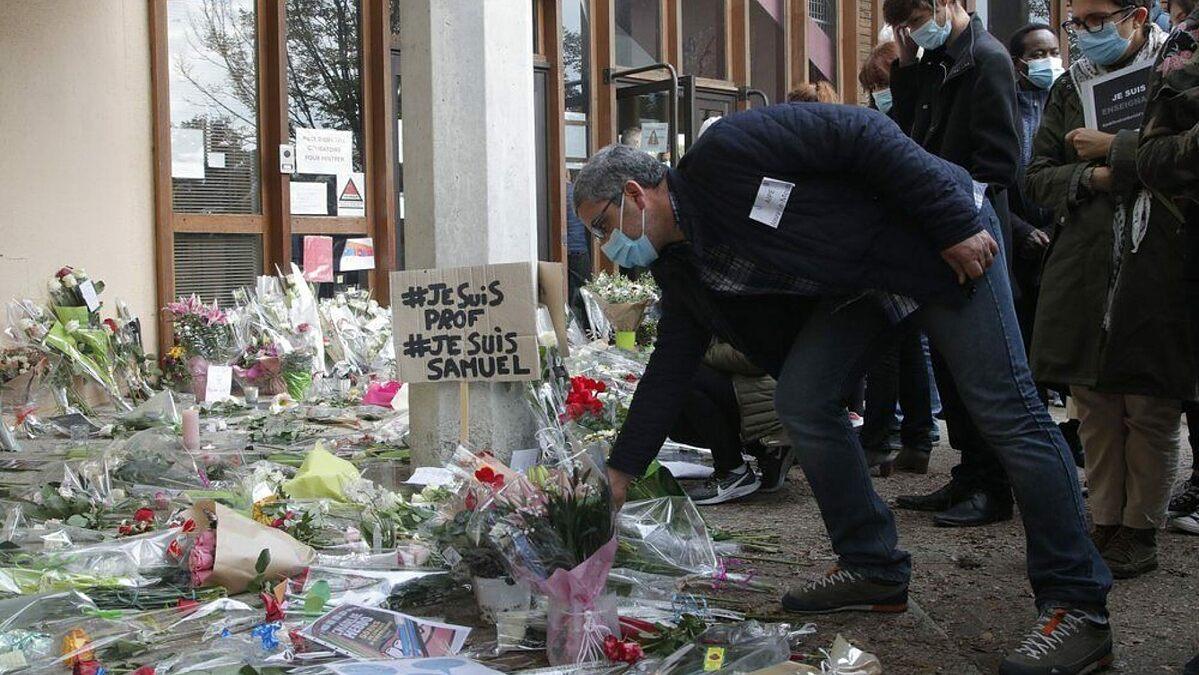 Một người đàn ông đặt hoa tưởng niệm thầy giáo Samuel Paty tại trường trung học ở Conflans Saint-Honorine, ngoại ô phía tây bắc Paris, hôm 17/10. Ảnh: AP.