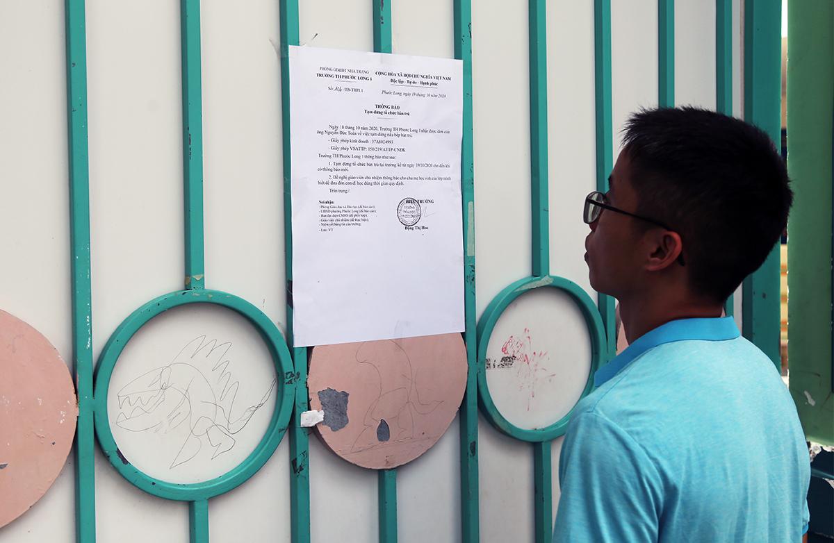 Phụ huynh đọc thông báo tạm dừng tổ chức bán trú trước cổng trường Tiểu học Phước Long 1, ngày 19/10. Ảnh: Xuân Ngọc.