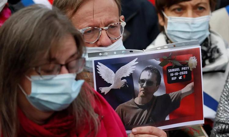 Một người cầm ảnh thầy giáo Samuel Paty trong lễ tưởng niệm ở Lille, miền bắc nước Pháp hôm 18/10. Ảnh: Reuters.