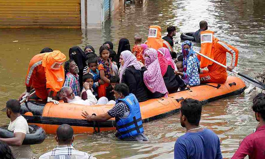 Cư dân được sơ tán khỏi một khu phố ngập lụt ở thành phố Hyderabad, Ấn Độ, hôm 15/10. Ảnh: Reuters.