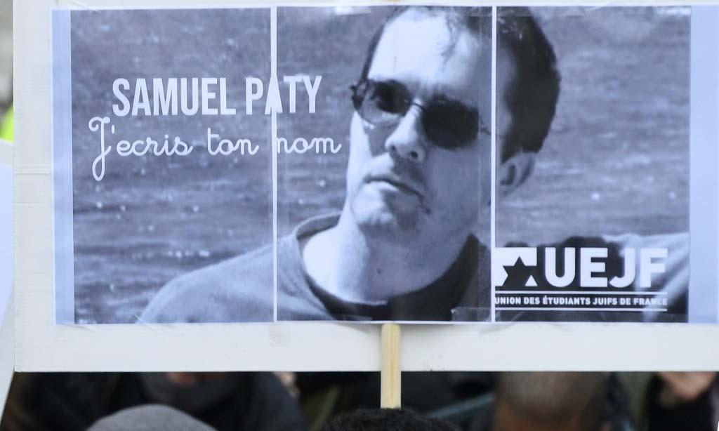 Một người cầm biển in ảnh của thầy giáo Samuel Paty trong cuộc tuần hành ở Paris, Pháp, hôm 18/10. Ảnh: AFP.