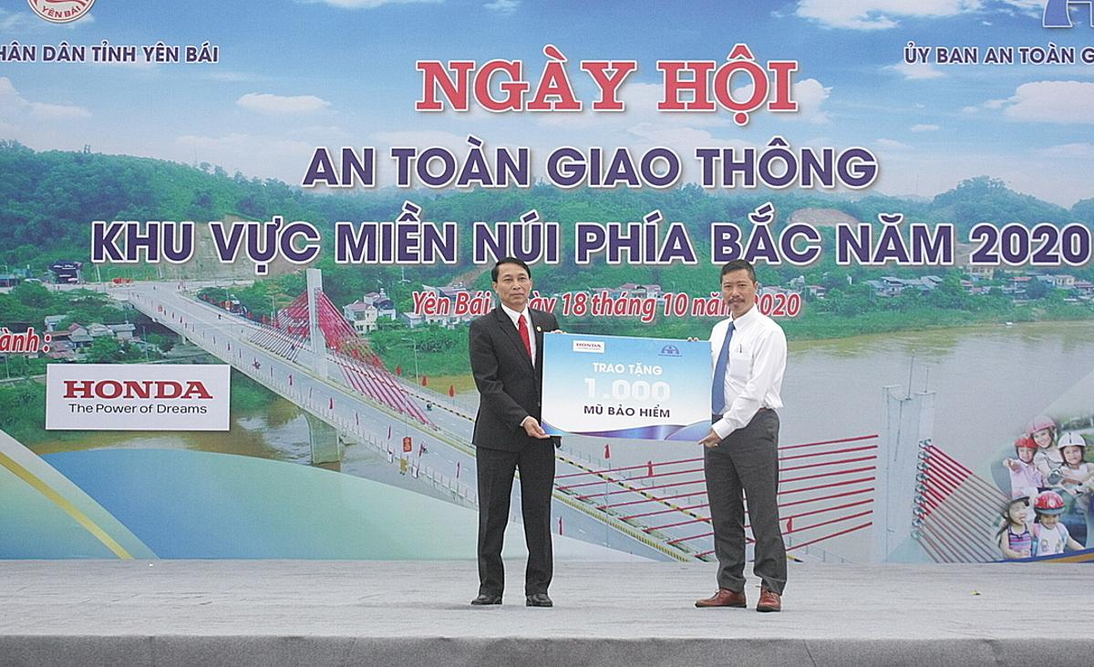 Ông Hoàng Quý Linh - Trưởng khối An toàn Công ty HVN trao tặng biển tượng trưng 1.000 mũ bảo hiểm cho đại diện tỉnh Yên Bái. Ảnh: Honda.