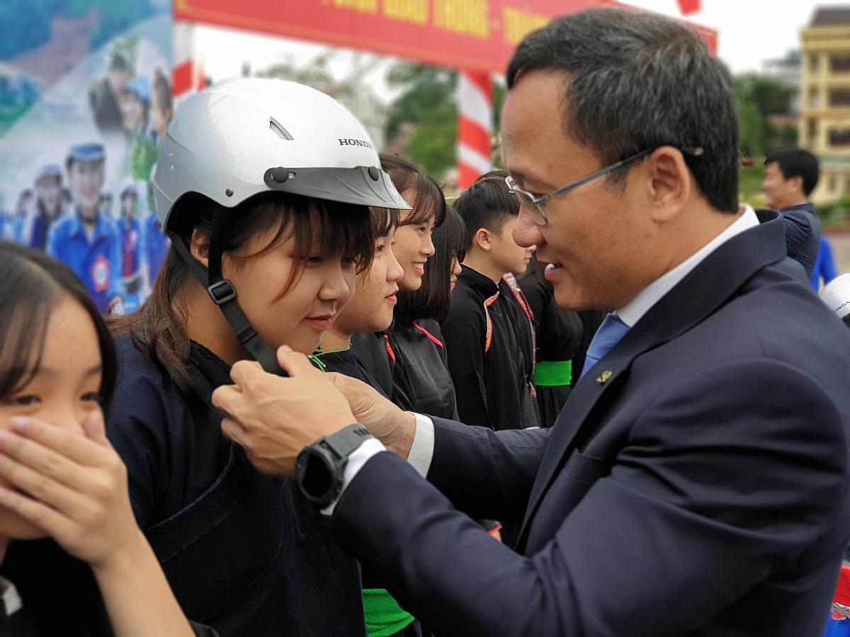 Ông Khuất Việt Hùng, Phó Chủ tịch Chuyên trách Ủy ban ATGT Quốc gia trao mũ cho đồng bào dân tộc Yên Bái. Ảnh: Honda.