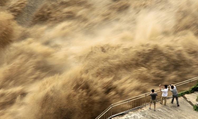Người dân theo dõi cảnh xả lũ đập Tam Môn Hạ ở tỉnh Hà Nam, Trung Quốc, ngày 30/6. Ảnh: AP.