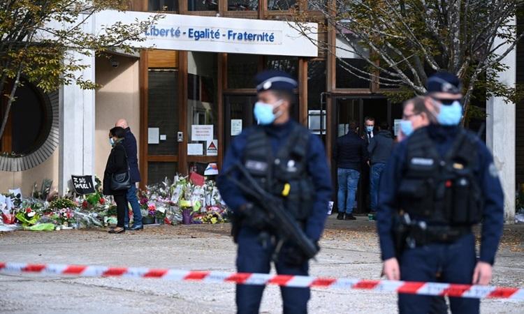 Cảnh sát phong tỏa bên ngoài trường trung học Bois dAulne hôm 19/10, phía sau là người dân đặt hoa tưởng nhớ thầy giáo Paty. Ảnh: AFP.