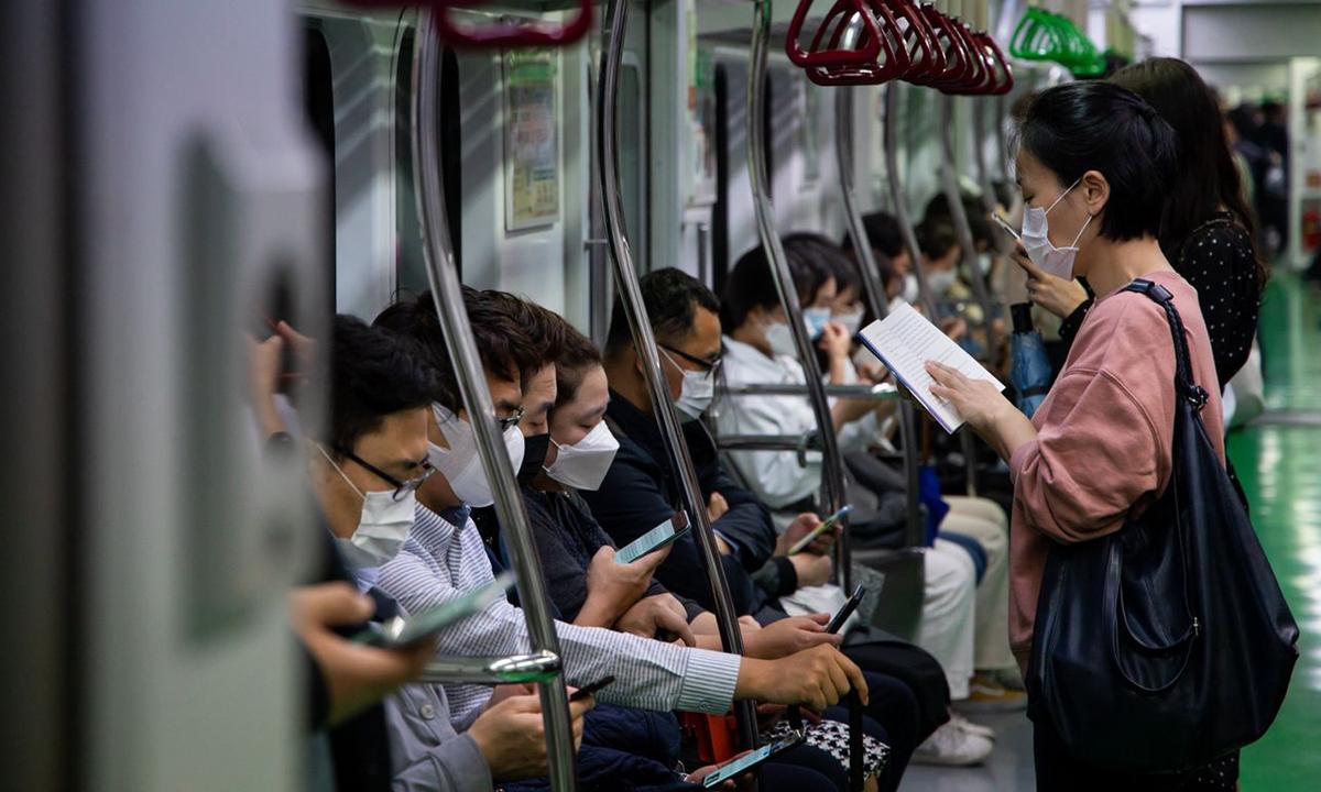 Tất cả hành khách đều đeo khẩu trang trên chuyến tàu điện ngầm ở Seoul, Hàn Quốc. Ảnh: Bloomberg News.