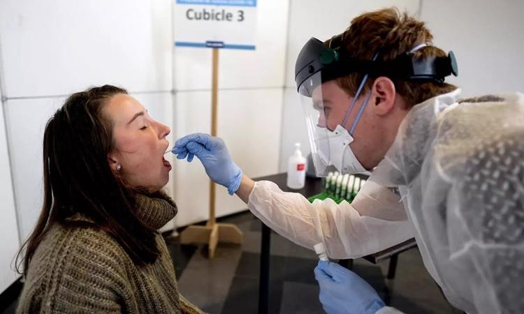 Nhân viên y tế lấy mẫu xét nghiệm nCoV cho một người dân tại Leuven, Bỉ, ngày 19/10. Ảnh: Reuters.