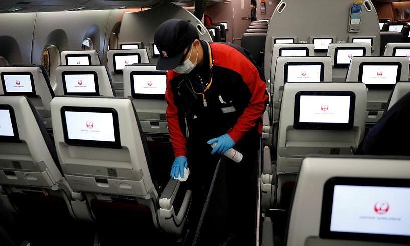Một nhân viên dọn vệ sinh máy bay Japan Airlines ngày 26/5. Ảnh: Reuters.