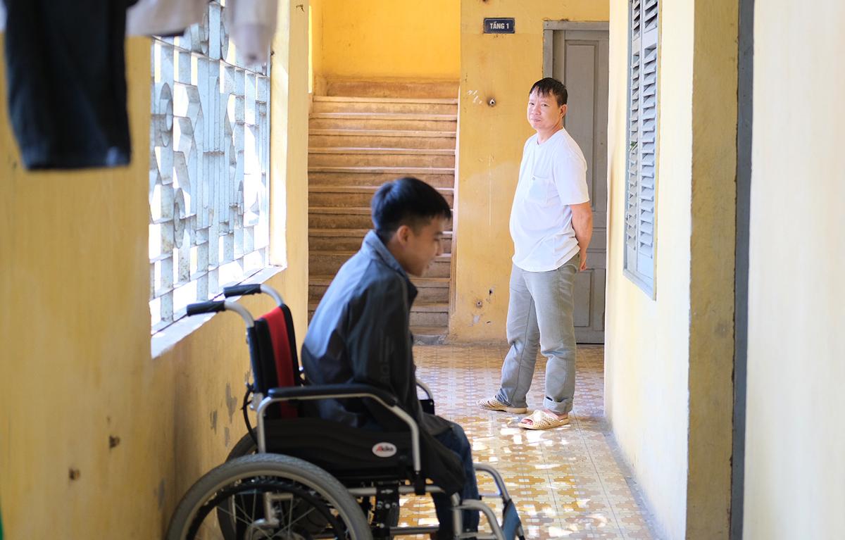 Ông Mây và Minh đứng ở hành lang trước phòng ký túc xá nói chuyện. Ảnh: Dương Tâm.