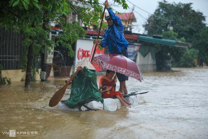 Người dân làm bè tạm đi chuyển về nơi tránh lũ an toàn tại thị trấn Kiến Giang, huyện Lệ Thủy, tỉnh Quảng Bình ngày 20/10. Ảnh: Hữu Khoa.