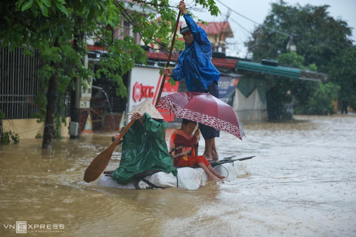 Người dân làm bè tạm đi chuyển về nơi tránh lũ an toàn tại thị trấn Kiến Giang, huyện Lệ Thủy, ngày 20/10. Ảnh: Hữu Khoa