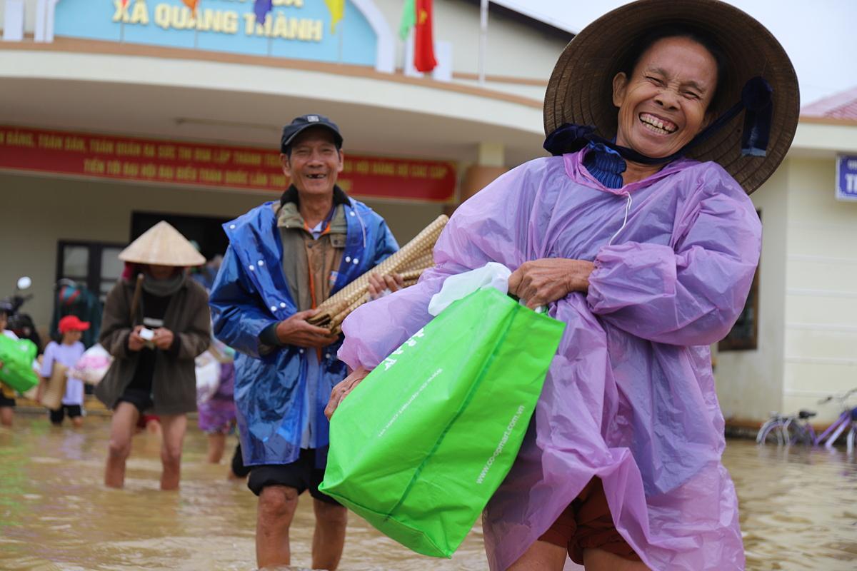 Một cụ bà xã Quảng Thành vui mừng nhận quà cứu trợ. Ảnh: Võ Thạnh.