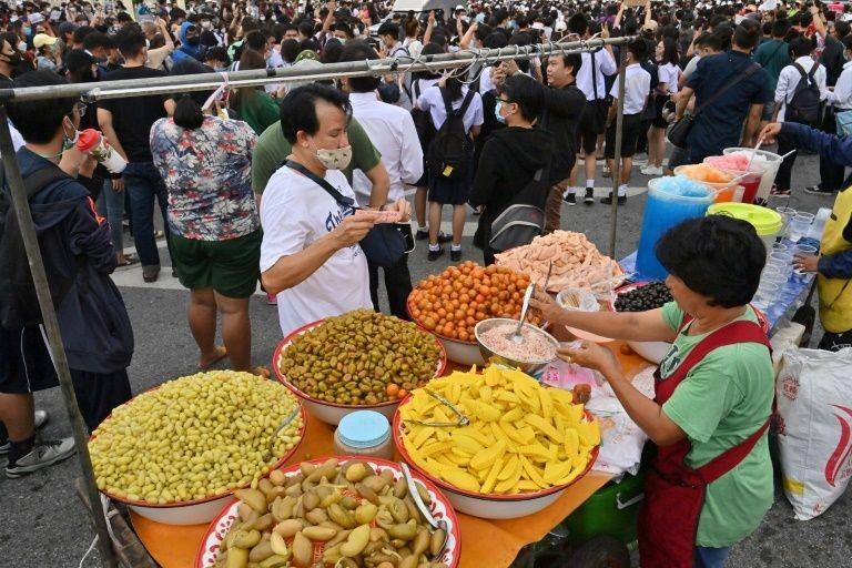 Một người đàn ông mua trái cây từ một quầy hàng rong trong cuộc biểu tình ở trung tâm Bangkok hôm 21/10. Ảnh: AFP.