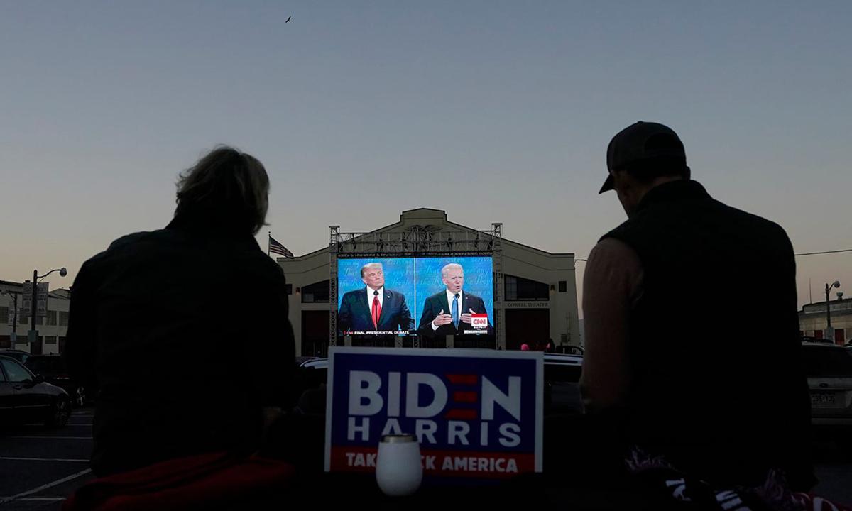 Hai người ngồi xem buổi tranh luận giữa Tổng thống Donald Trump và ứng viên Joe Biden tại thành phố San Francisco, bang California hôm 22/10. Ảnh: AP.