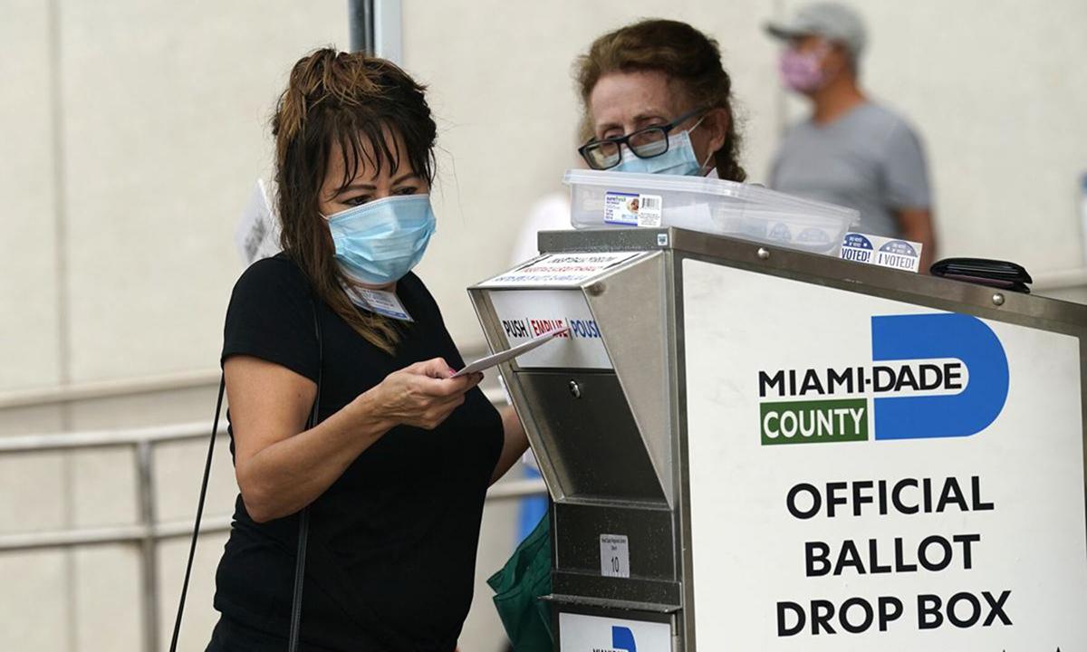 Một nữ cư tri đứng trước điểm bỏ phiếu sớm ở Miami, bang Florida hôm 19/10. Ảnh: AP.
