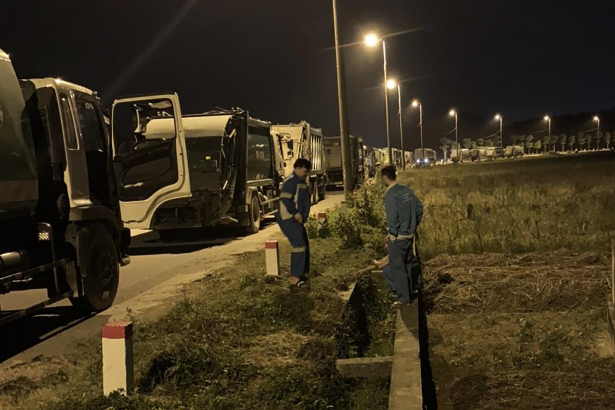 Xe rác xếp hàng dài trước cổng số 2 bãi rác Nam Sơn tối 23/10.  Ảnh: Nguyễn Bình.