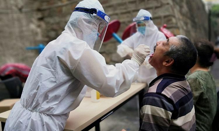 Nhân viên y tế lấy mẫu xét nghiệm nCoV cho một người dân ở Tân Cương hồi tháng 7. Ảnh: Reuters.