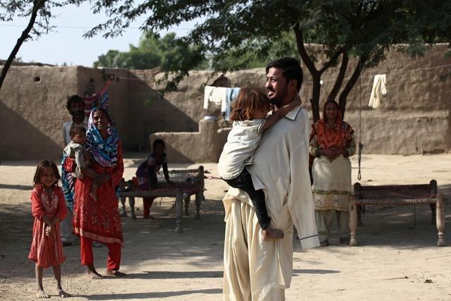 Ikram chơi cùng em gái tại nhà ở Samundri hôm 20/10. Ảnh: Reuters