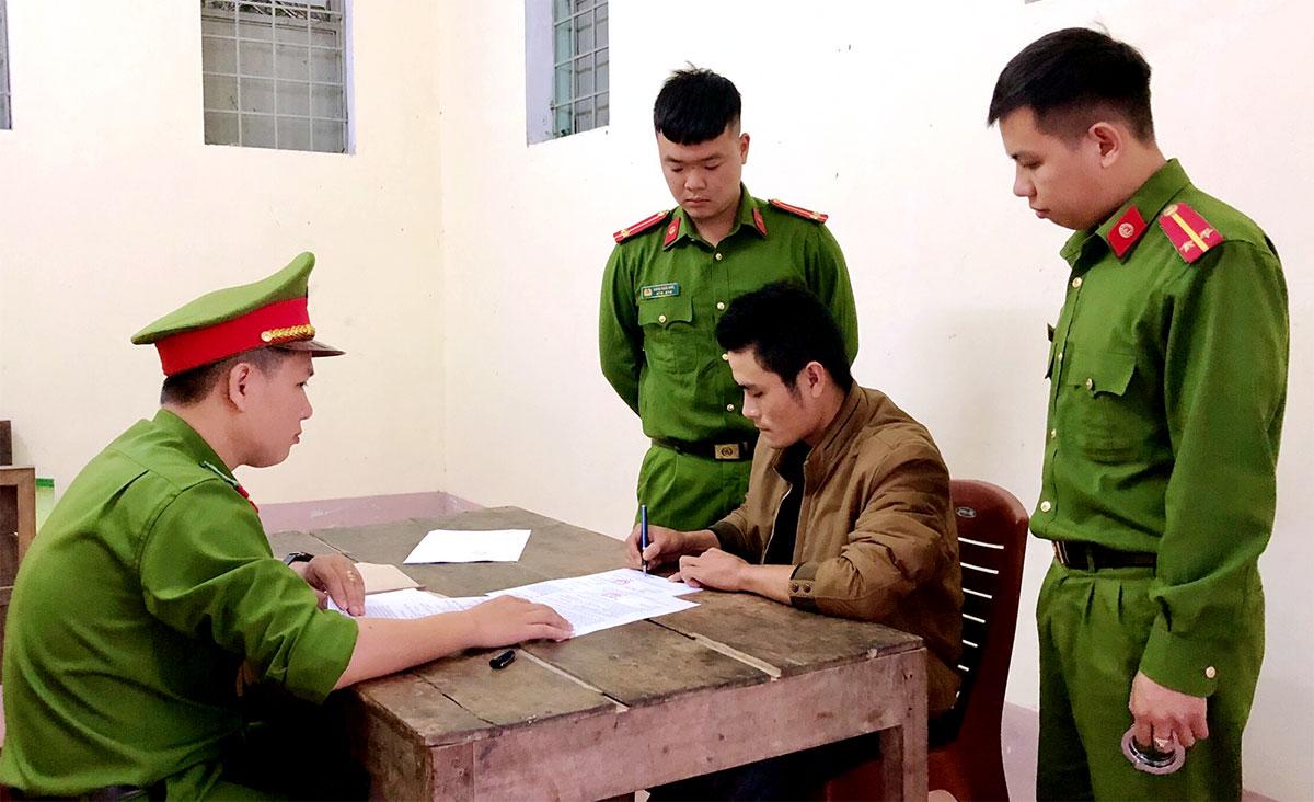 Nghi can Kiên (mặc áo khoác màu nâu) làm việc với cảnh sát. Ảnh: Hùng Lê